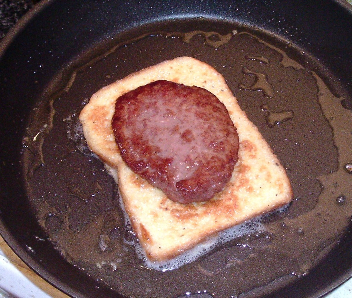 Blue beef burger is laid on one of the slices of eggy bread