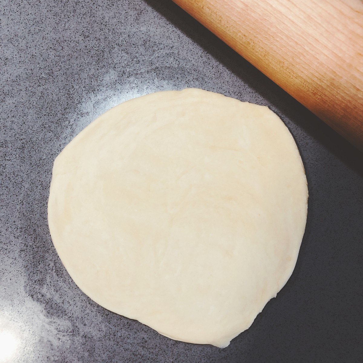 Use a rolling pin to stretch the dough as thin as you can.