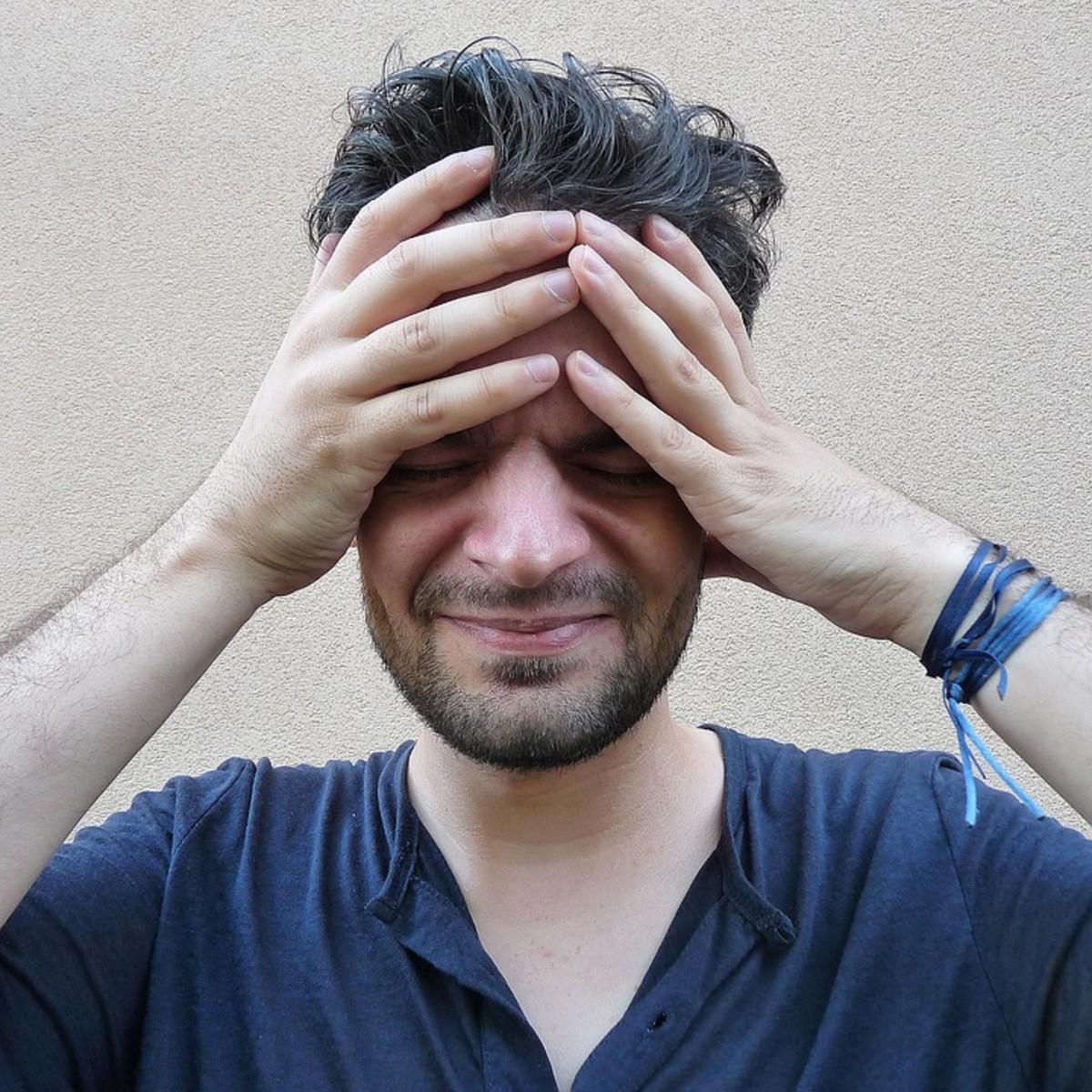 Headache sufferer cradles his throbbing head