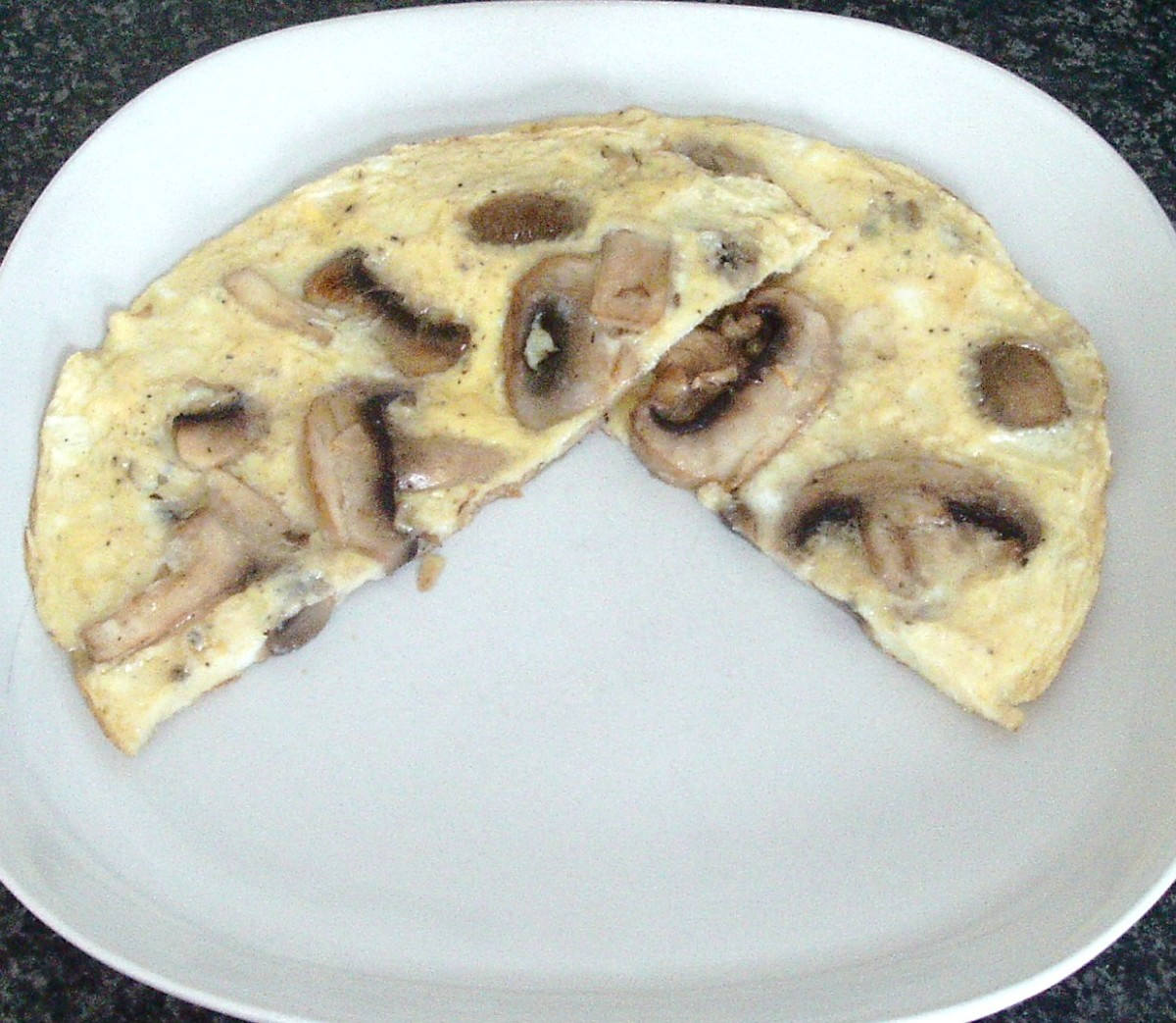 Garlic mushrooms tortilla is sliced in half and plated