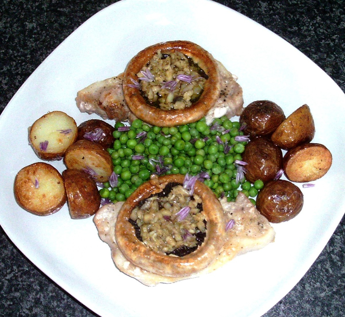 Pan fried pork loin fillets are served with garlic stuffed mushrooms, potatoes and peas