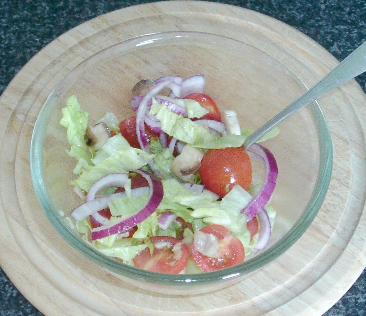 Salad ingredients are stirred through seasoned oil