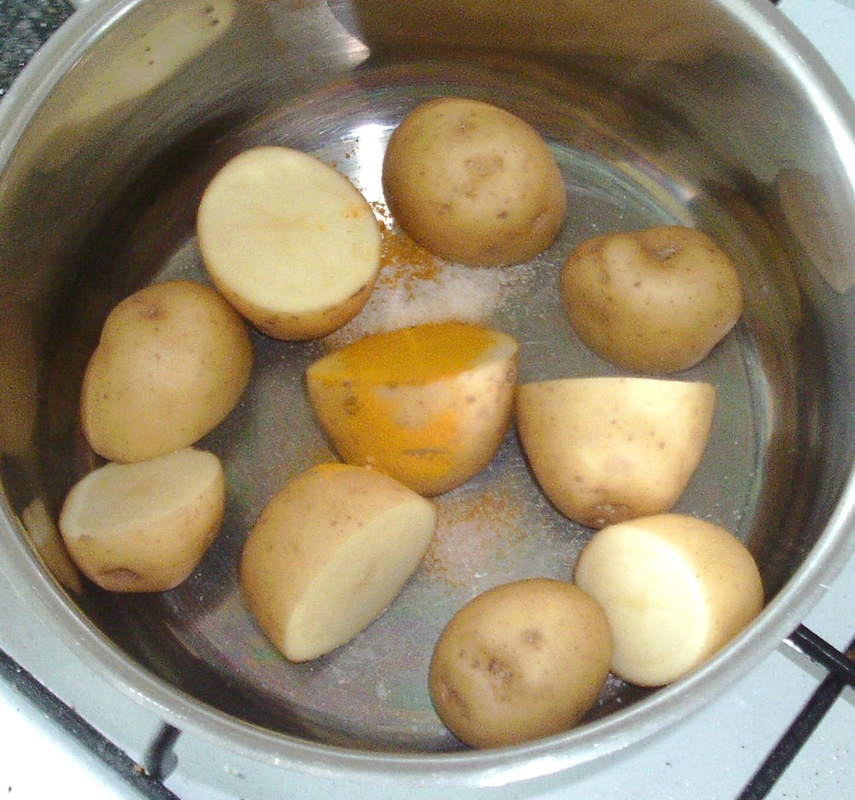 Salt and turmeric are added to prepared potatoes