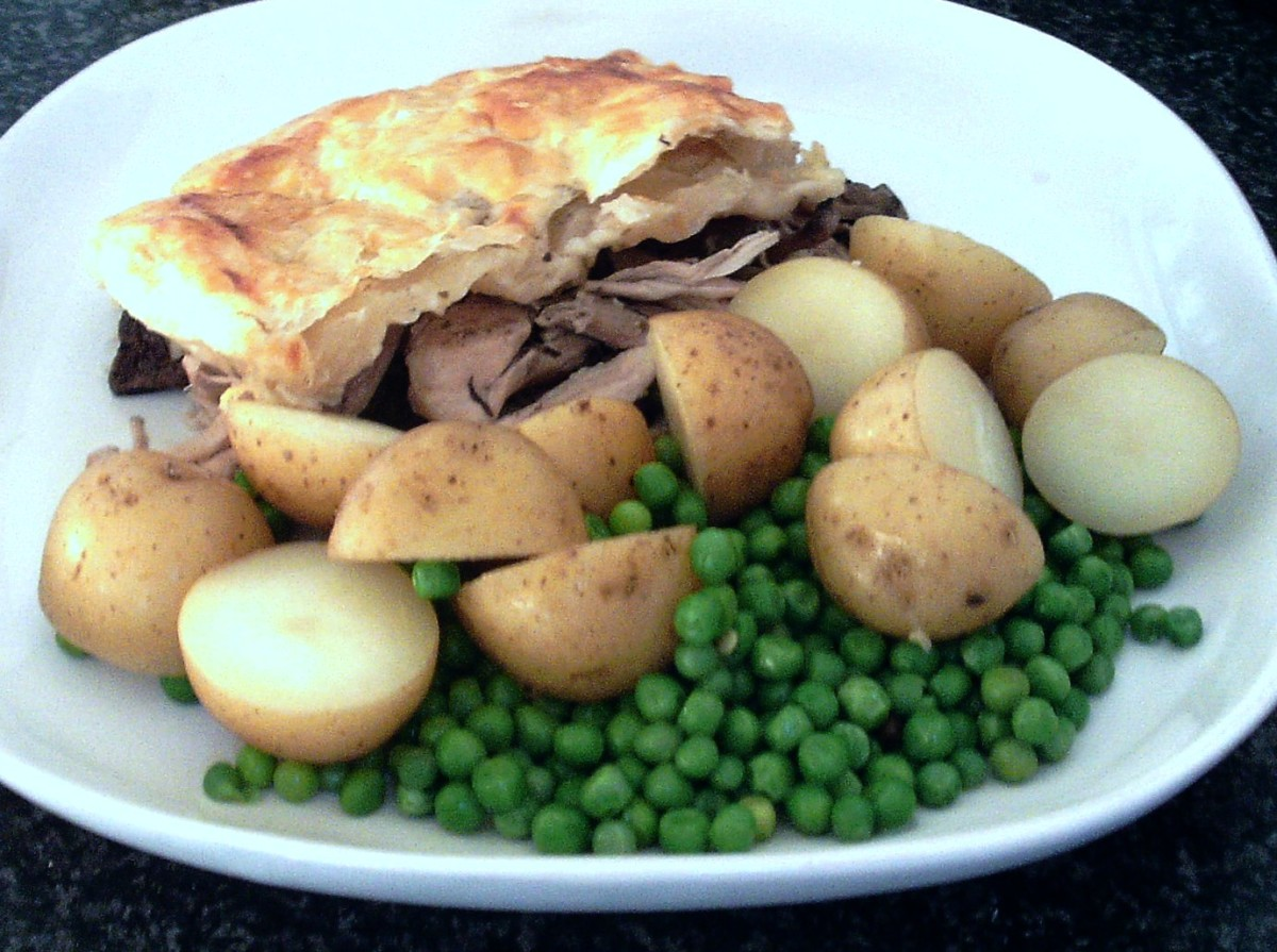 Chicken and garlic mushrooms puff pastry pie with new potatoes and peas