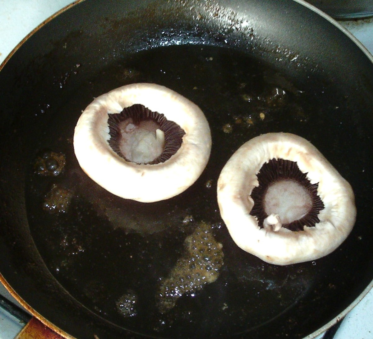 Mushroom cups are added to frying pan