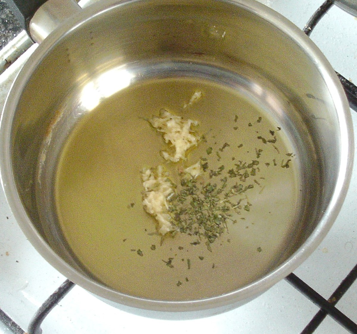 Garlic and herbs are added to oil in saucepan