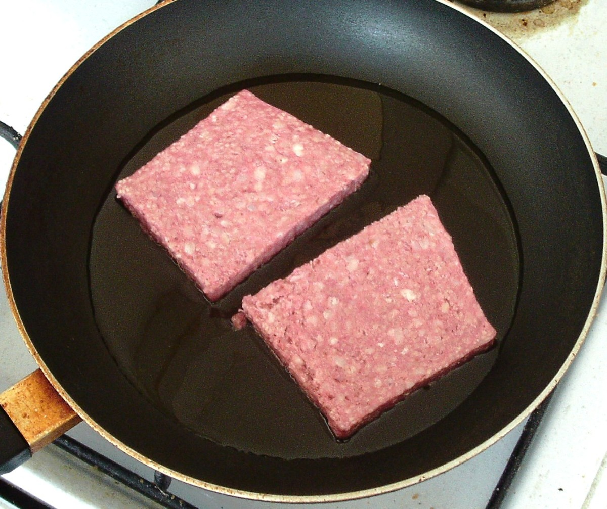 Sliced sausages are added to hot frying pan
