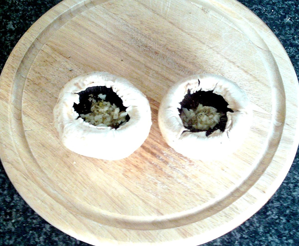Grated garlic and seasonings are added to mushroom cavities