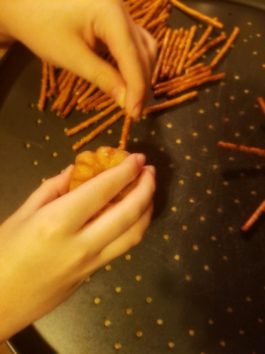Carefully push pretzel sticks into donut. Eight per donut.