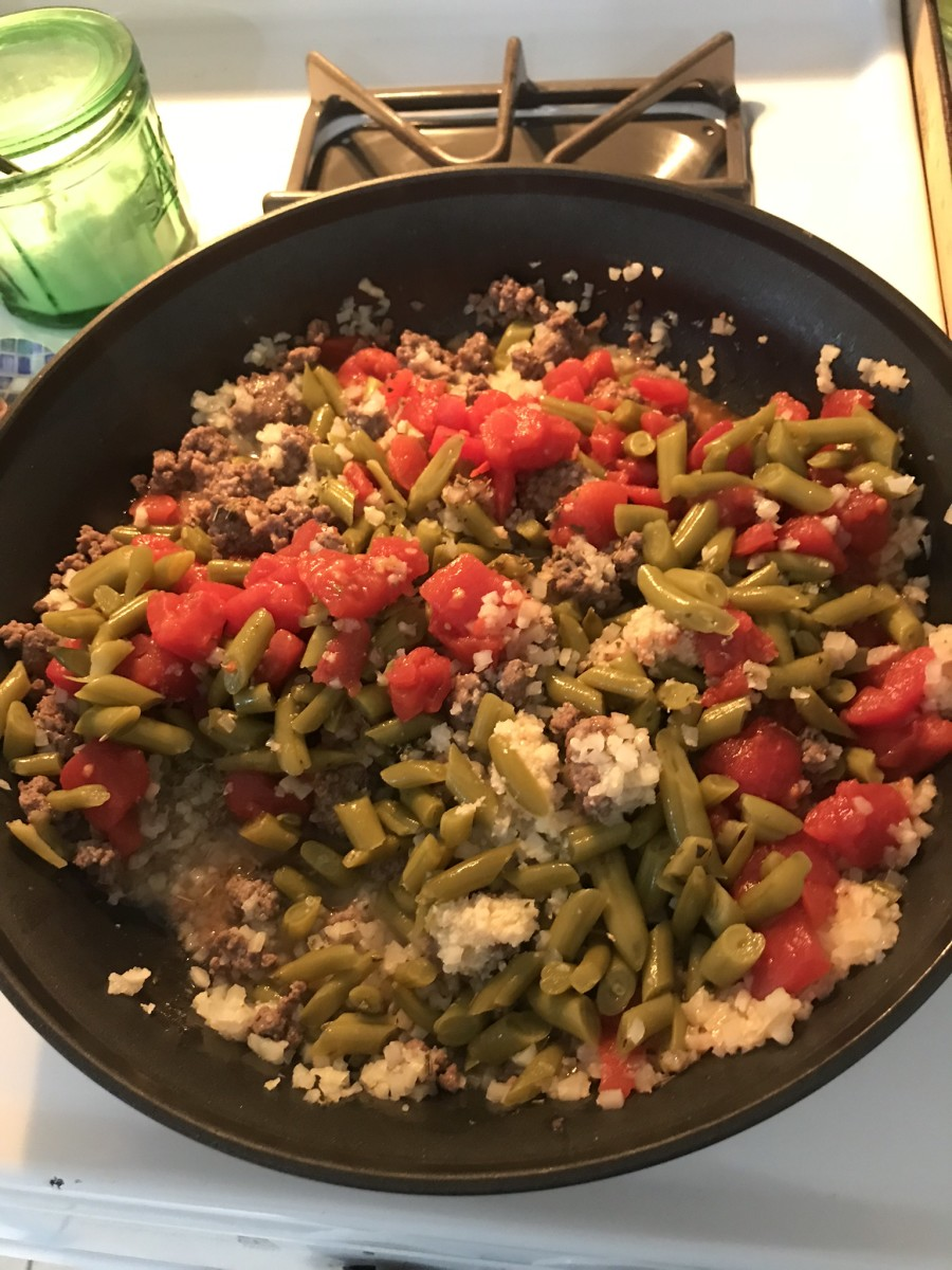 Added cauliflower rice, green beans, tomatoes, and seasoning to the beef.