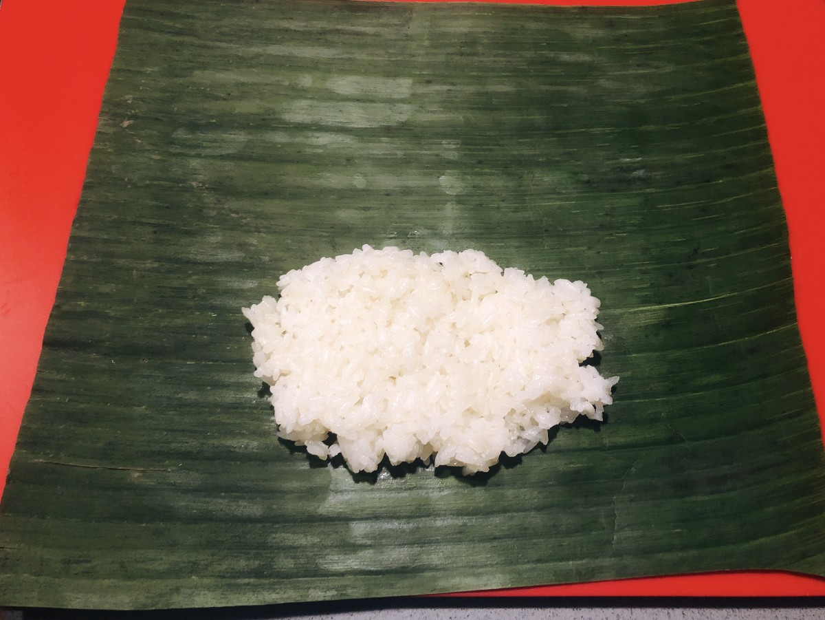 Place two tablespoons of steamed rice over the banana leaf.