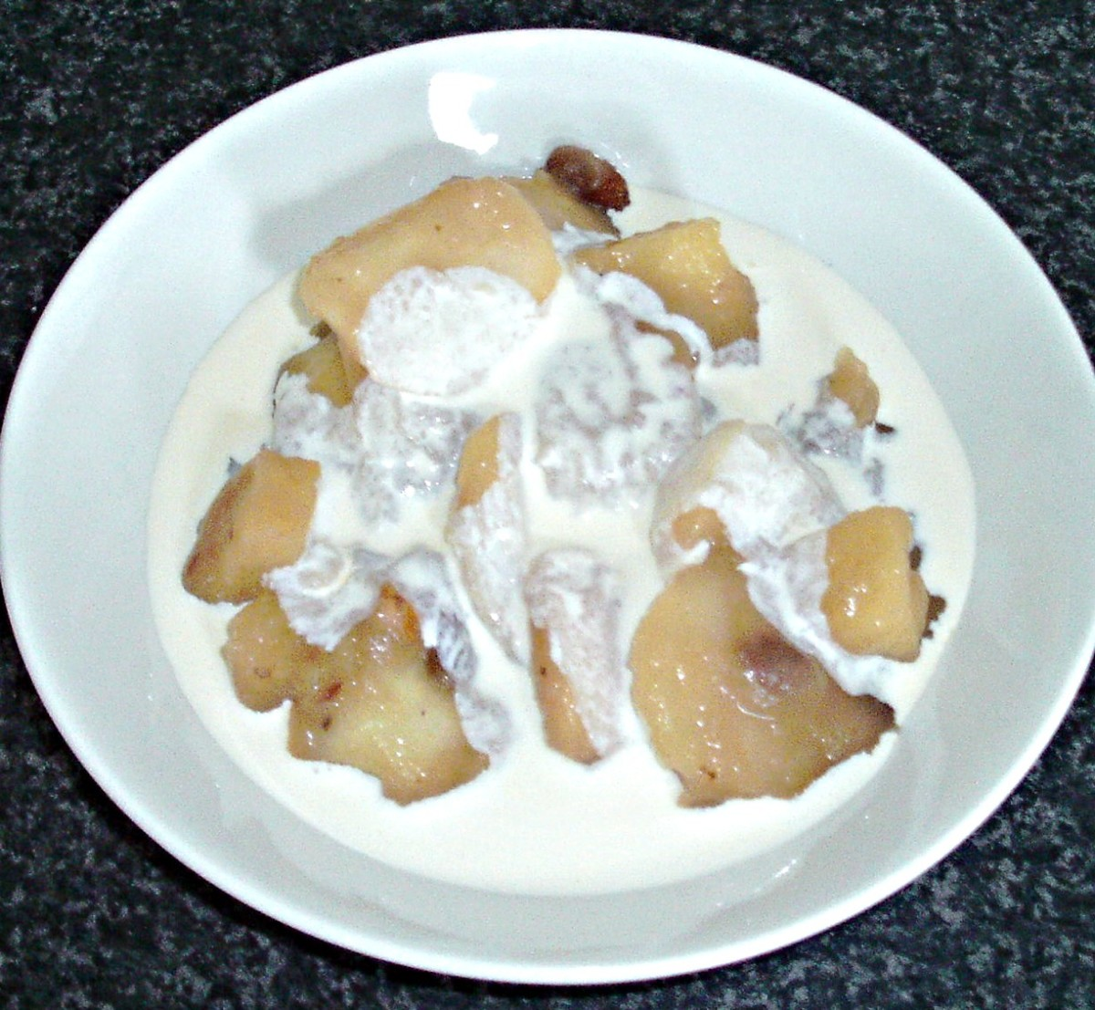 Fresh cream is poured over stewed apples and pineapple with mincemeat