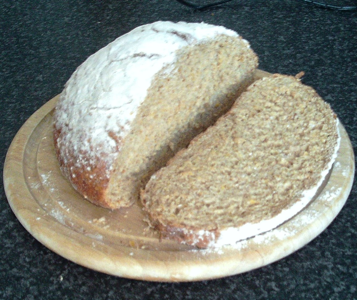 A thick slice is cut from a wheat, spelt and rye loaf