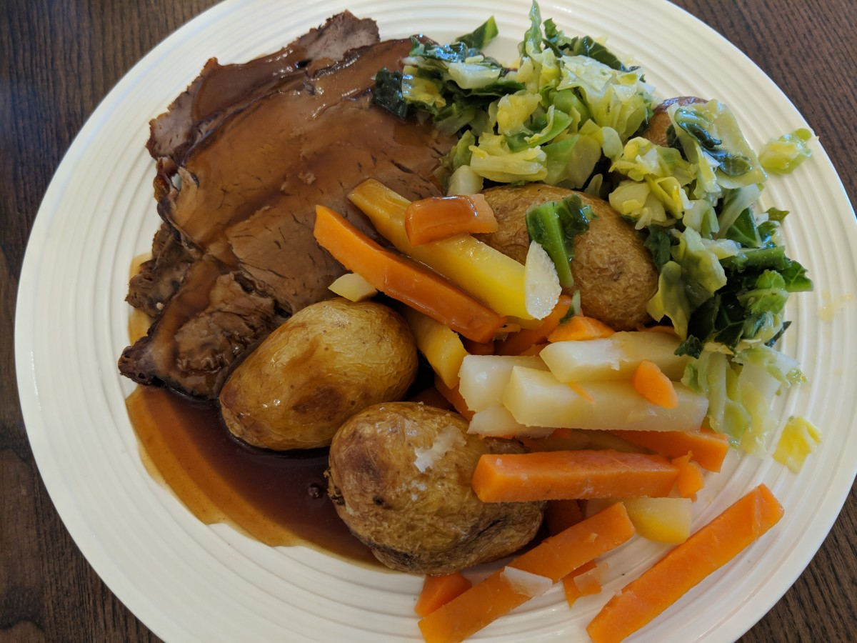 A traditional plate of roast beef, gravy and vegetables.