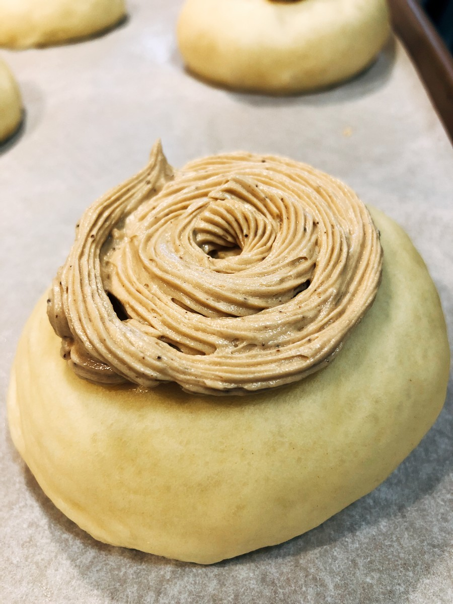 Use a piping bag to pipe the coffee topping on every dough ball. Use a spiral motion.