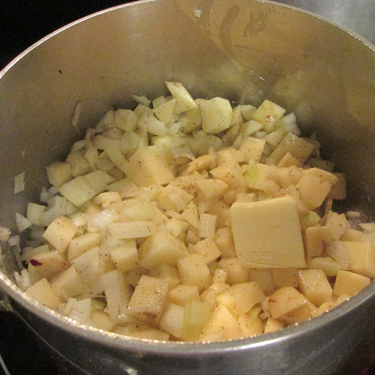 The onions, seasonings, and potatoes cooking with butter.
