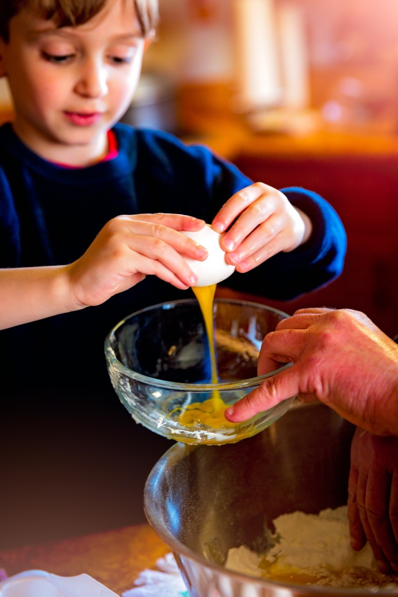 a child cracking eggs into a bowl