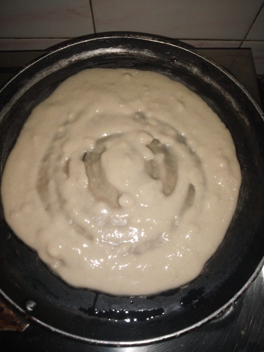 Heat tawa (pan), drizzle oil or ghee, add a ladle full of batter, and make dosa. Cover and cook.