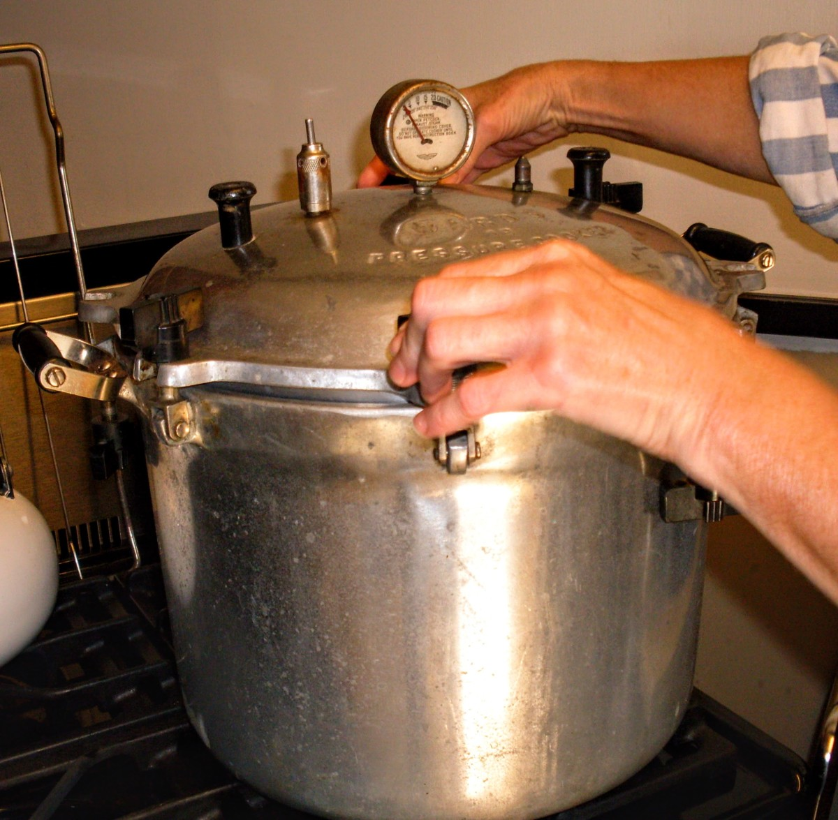 Screw or fasten lid in place. On old-style canners, screw knobs down tightly in opposites, to achieve an even seal.