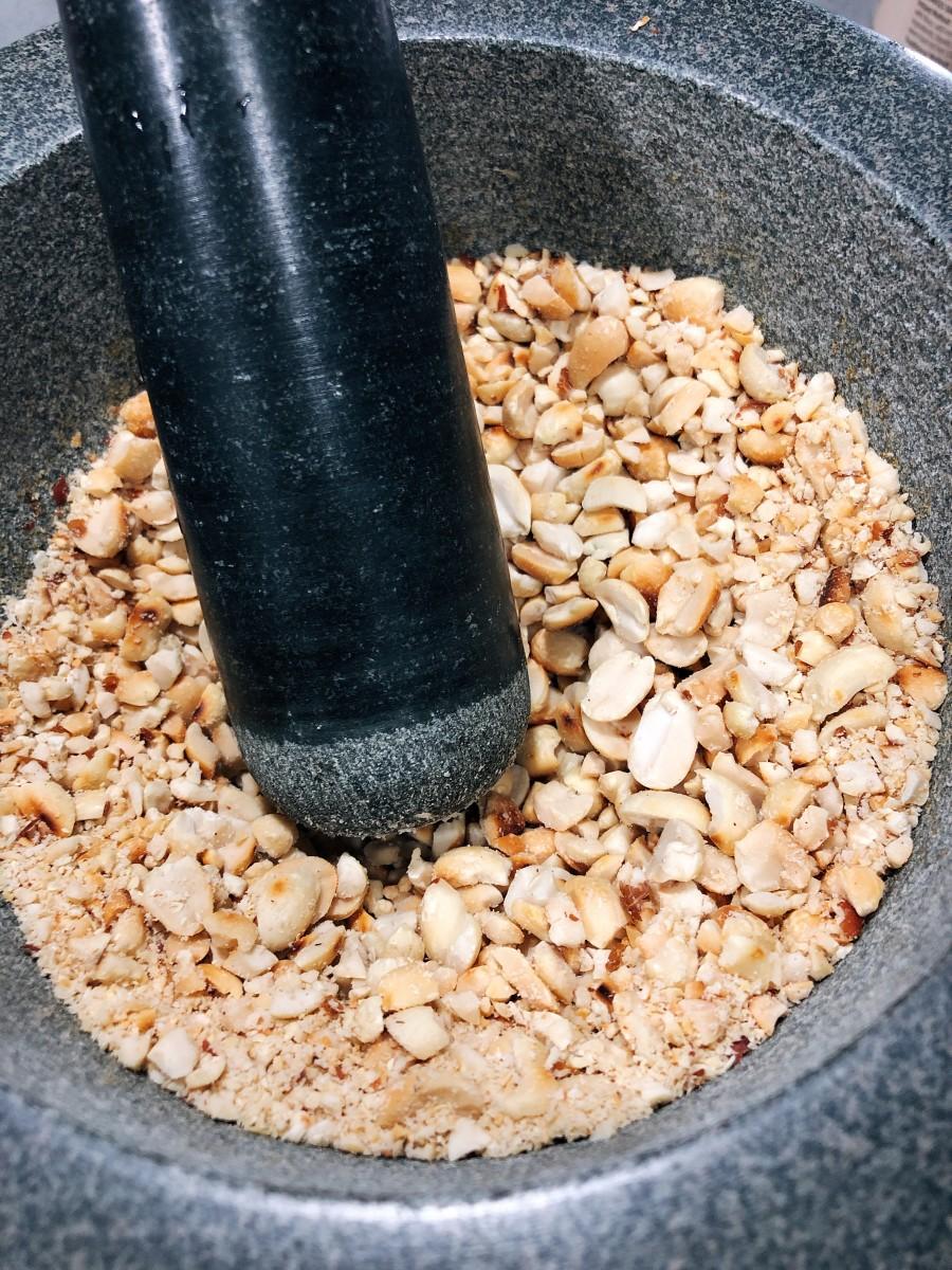 Add the peanuts into the mortar.