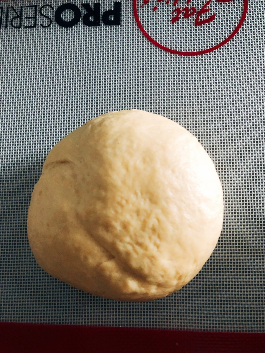 Transfer the dough onto a floured surface and continue kneading with your hands for another 10 minutes, or until it is smooth.
