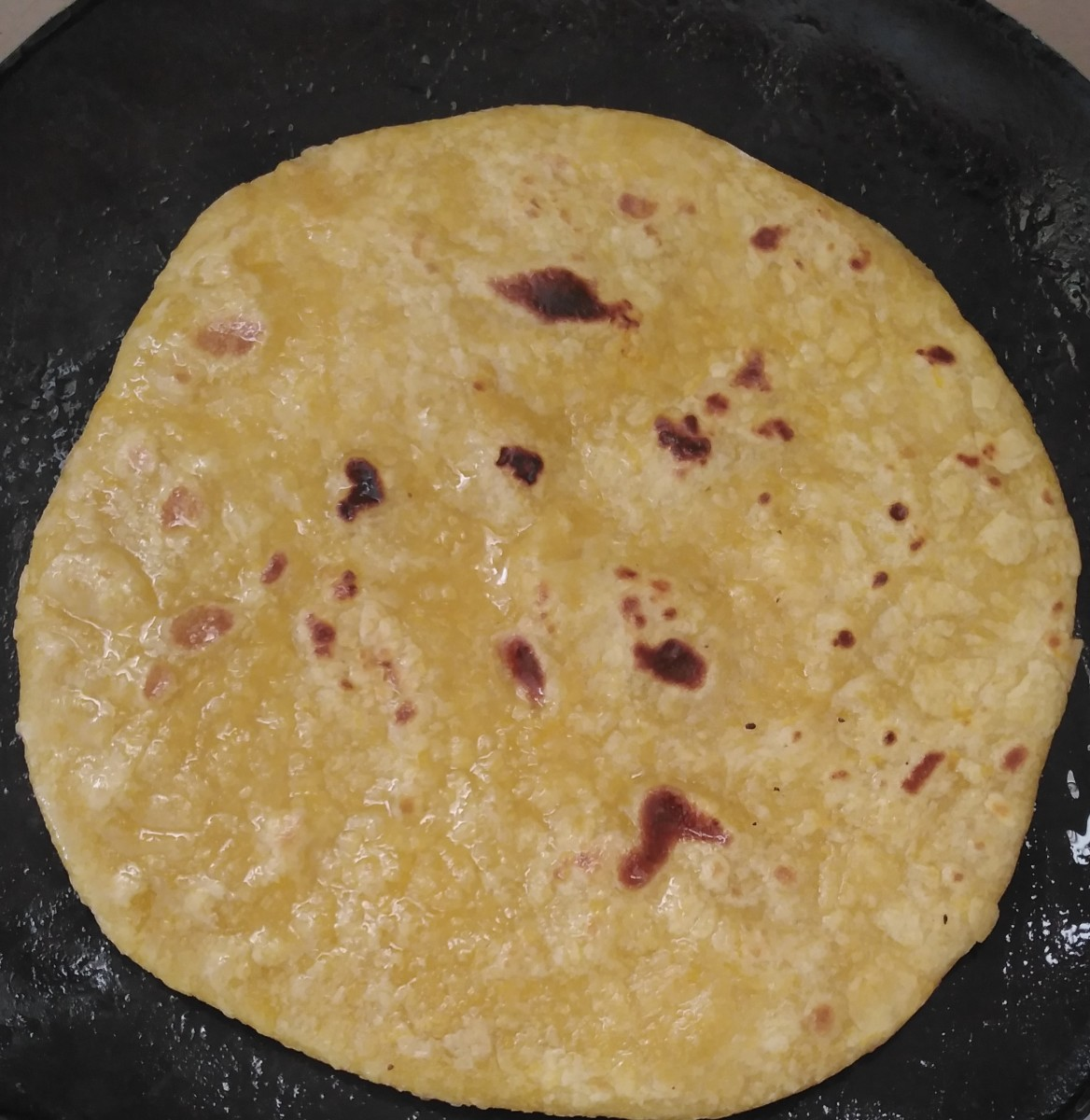 Apply 1 tablespoon of oil on the cooked side. After 1 minute, flip it and apply oil on the other side.