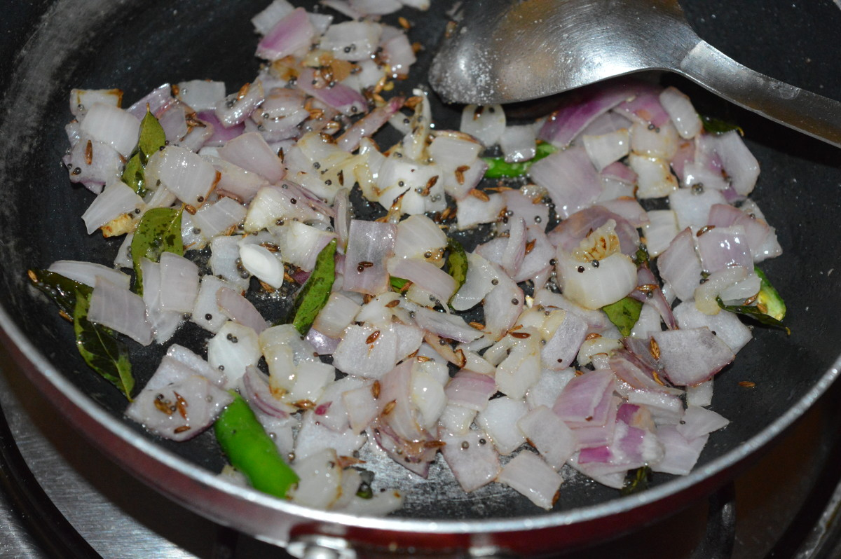 Step three: Add chopped onions, slit green chilies, and some salt. Continue sauteing until onions turn pinkish.