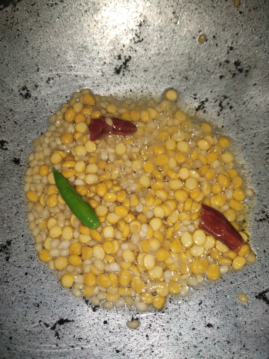 Add urad dal and chana dal. Fry until brown. Add green and red chilies.