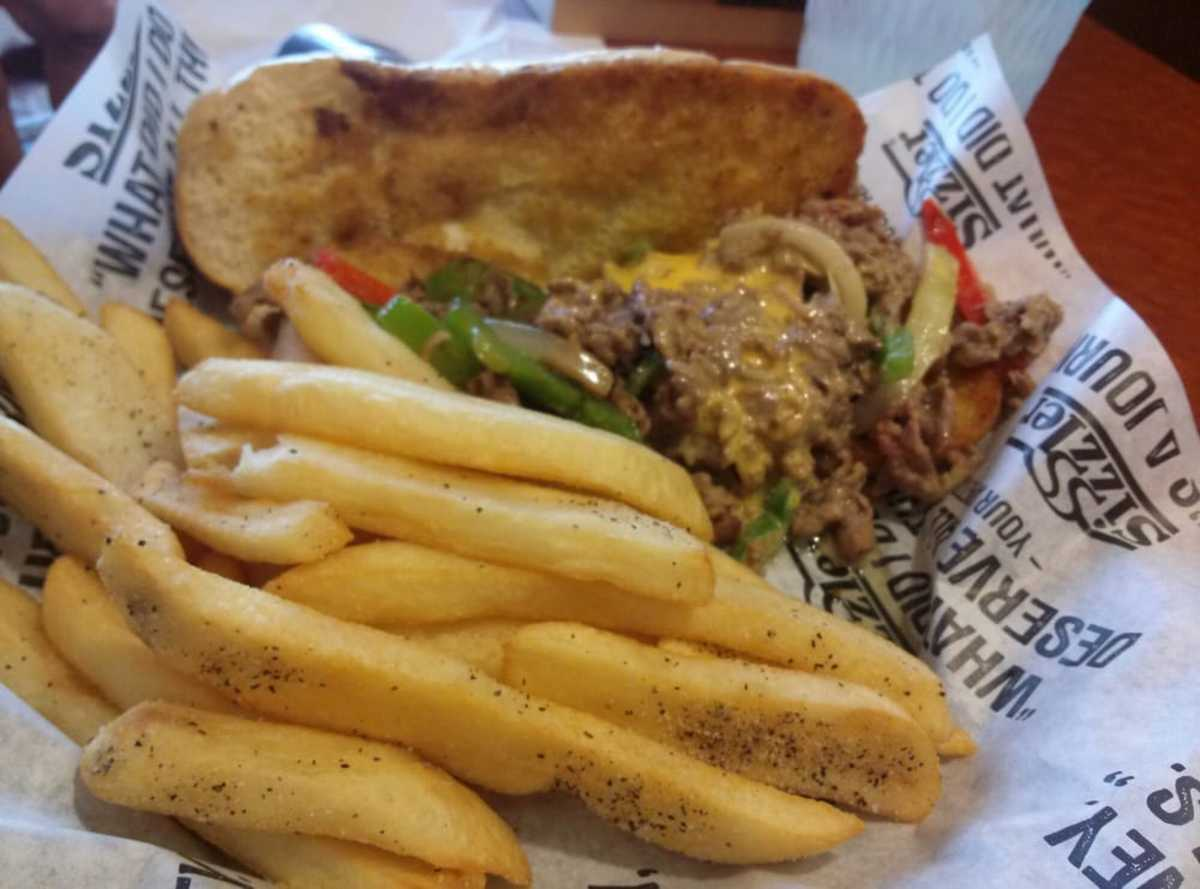 A Sizzler cheesesteak with fries