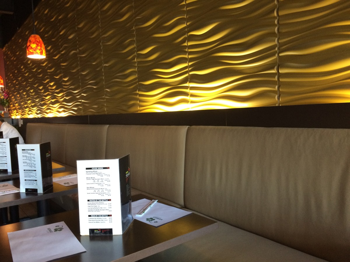 A golden-yellow textured wall inside of Kenko Sushi
