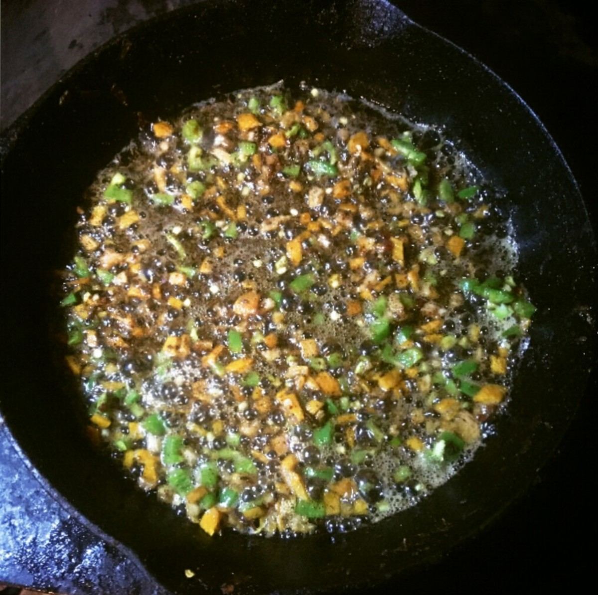 The spices, orange, and peppers simmer briefly by themselves in butter. The heat must be low, or they will burn. A minute or two of cooking is enough; you only want to blend flavors.
