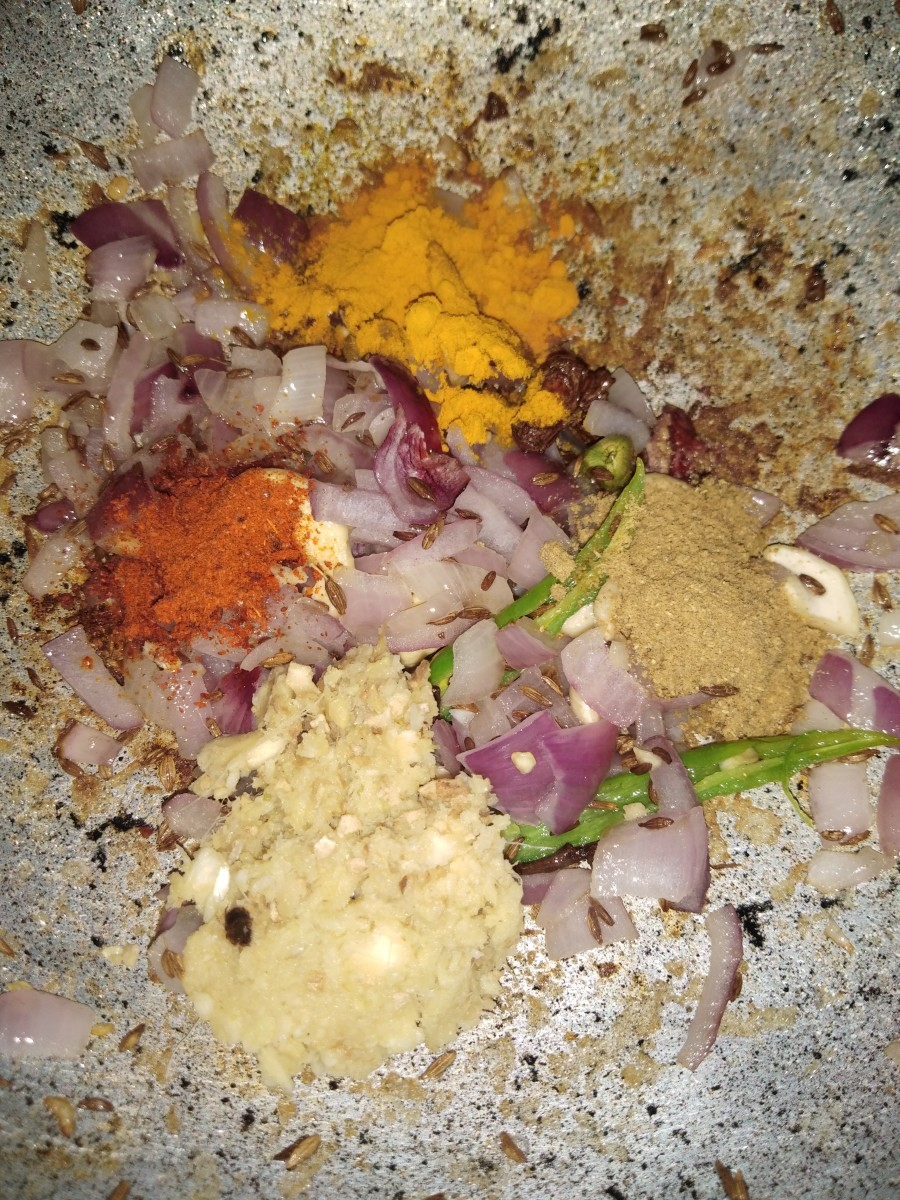 Add ginger-garlic paste and dry masalas (i.e., turmeric powder, red chili powder, coriander powder). Mix everything properly. Saute until the raw smell of the ginger-garlic goes away.