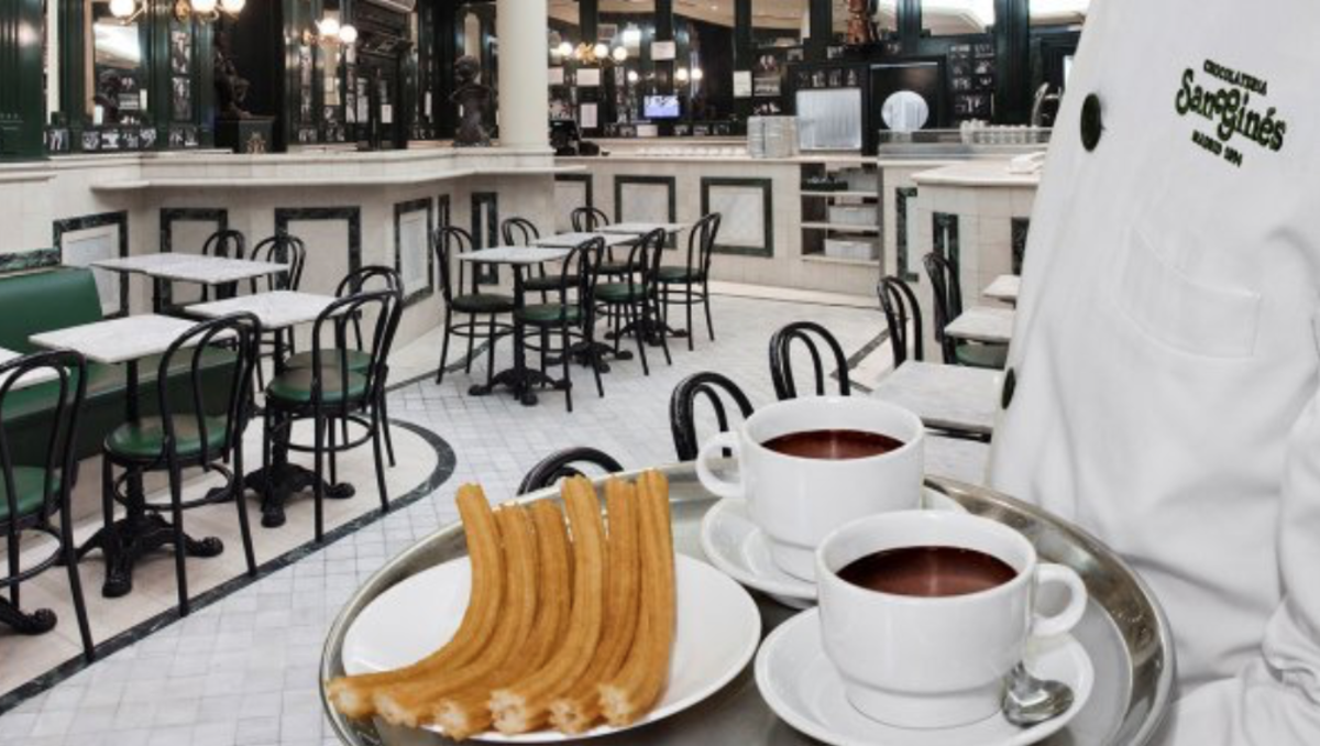 Inside view of El Café San Gines as a server, or un mesero, delivers a plate of churros con chocolate.