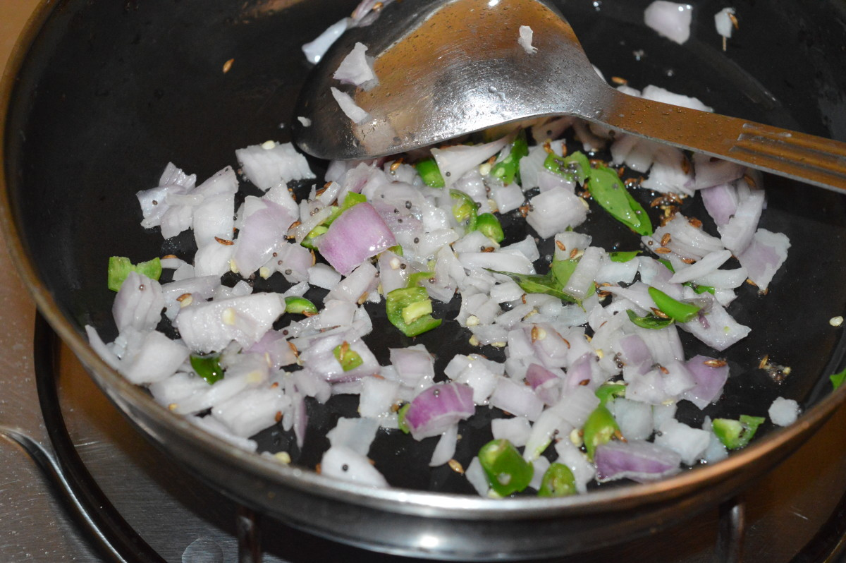 Step two: Add chopped onions and slit green chilies. Continue the sauteing until onions turn pinkish.