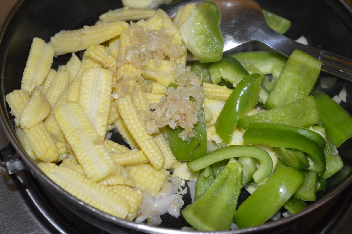 Step two: Throw in the parboiled baby corn, capsicum, and ginger-garlic paste. Add some salt. Mix well. Saute the mixture until you get a nice aroma.