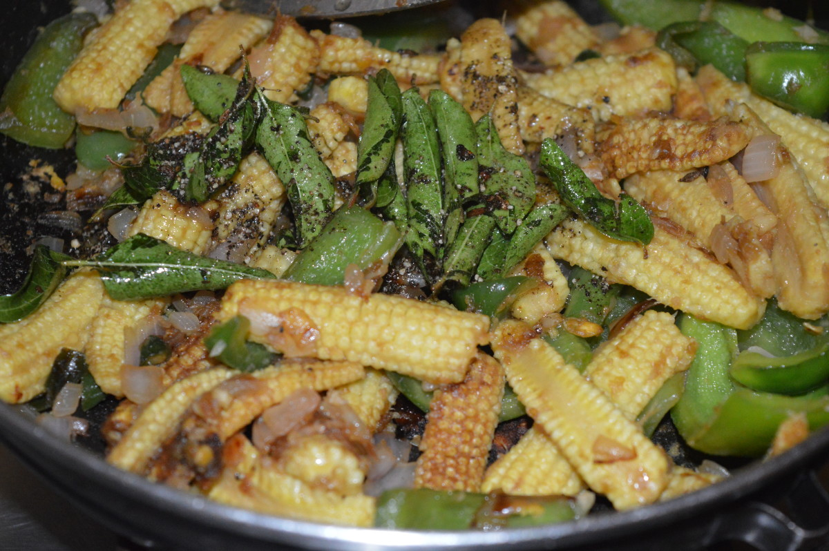 Pour the seasoning on the baby corn capsicum fry mixture.