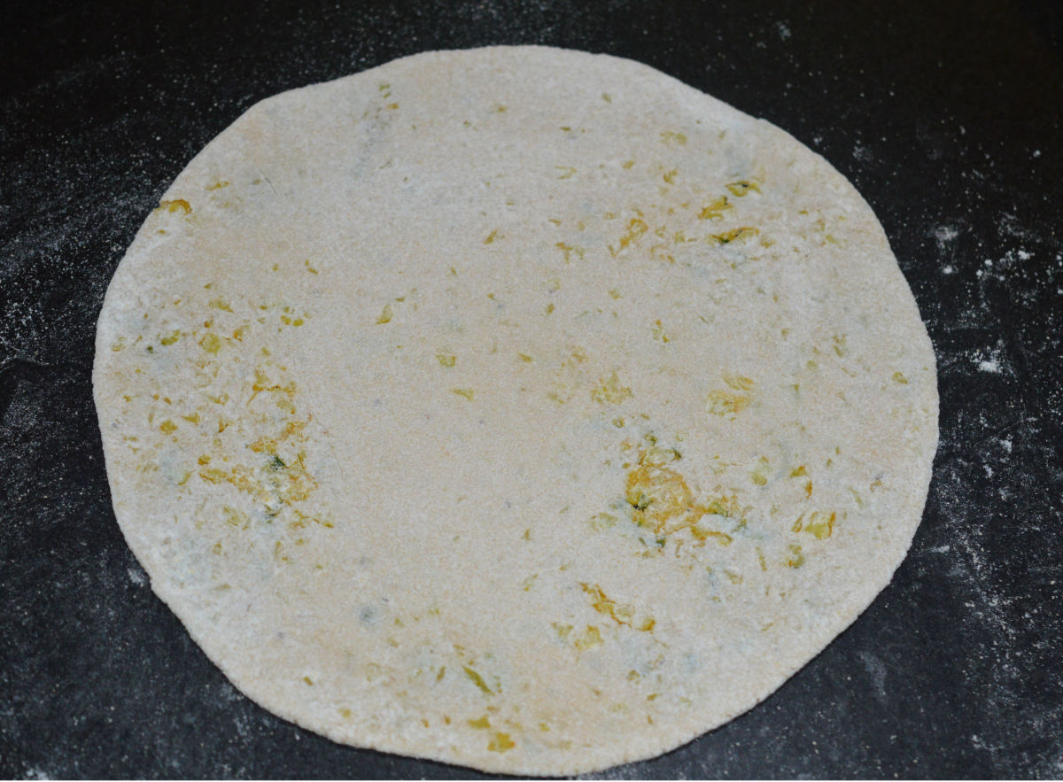 Roll, while dipping in wheat flour to get a 5-6 inch diameter disc.