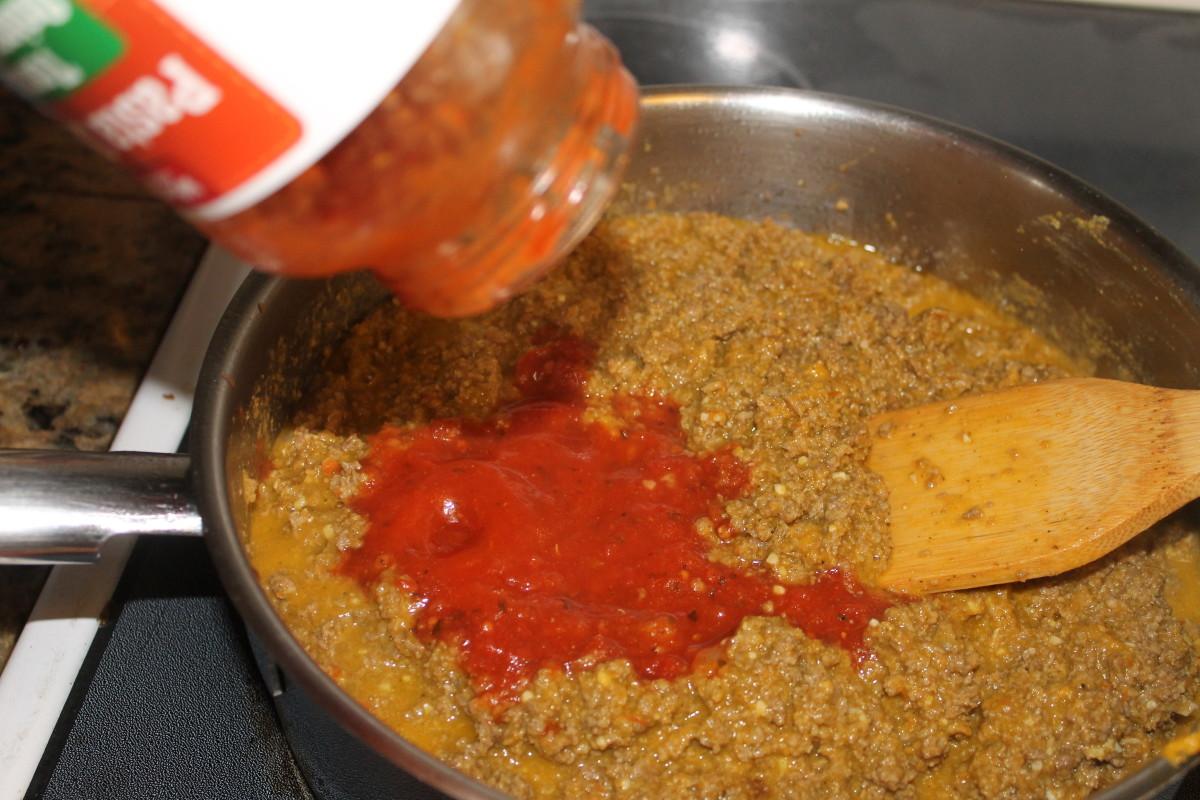 Adding pasta sauce.