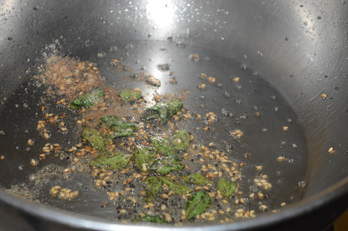 Step six: For making the seasoning, heat the oil in a large pan. Add mustard seeds, sesame seeds, curry leaves, and hing powder. Saute until mustard seeds pop. Turn off heat.