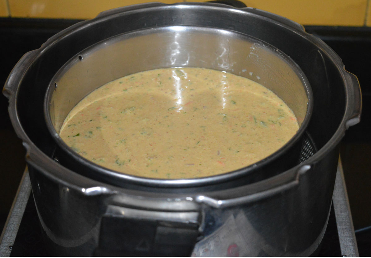 Step three: Check the consistency of the batter. If it is thick, add some water and mix well to bring it to the idli batter consistency. Add lemon juice and fruit salt or baking soda. Gently mix the batter once. Quickly pour it into the greased tin.