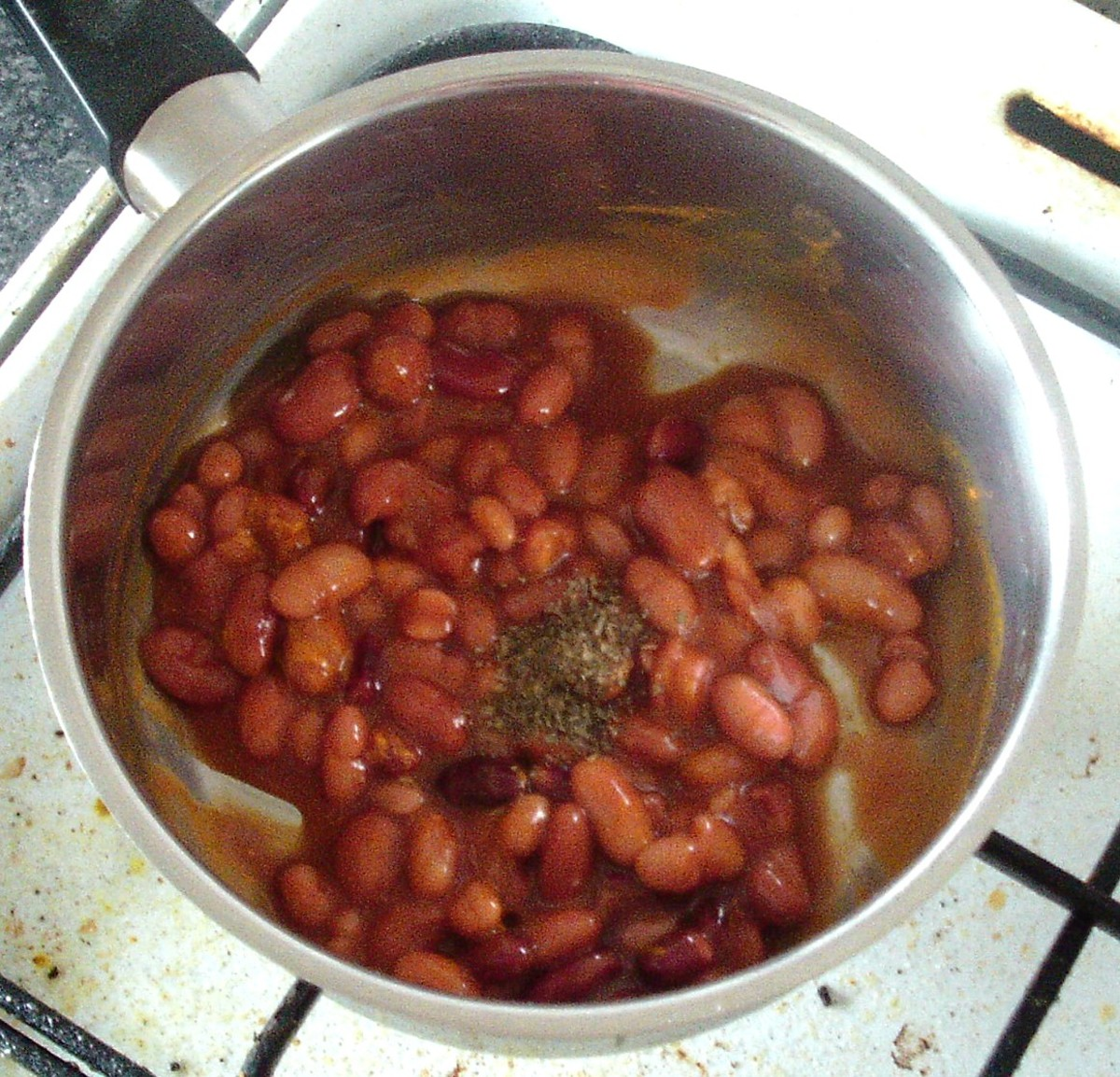 Dried herbs are added to beans in saucepan