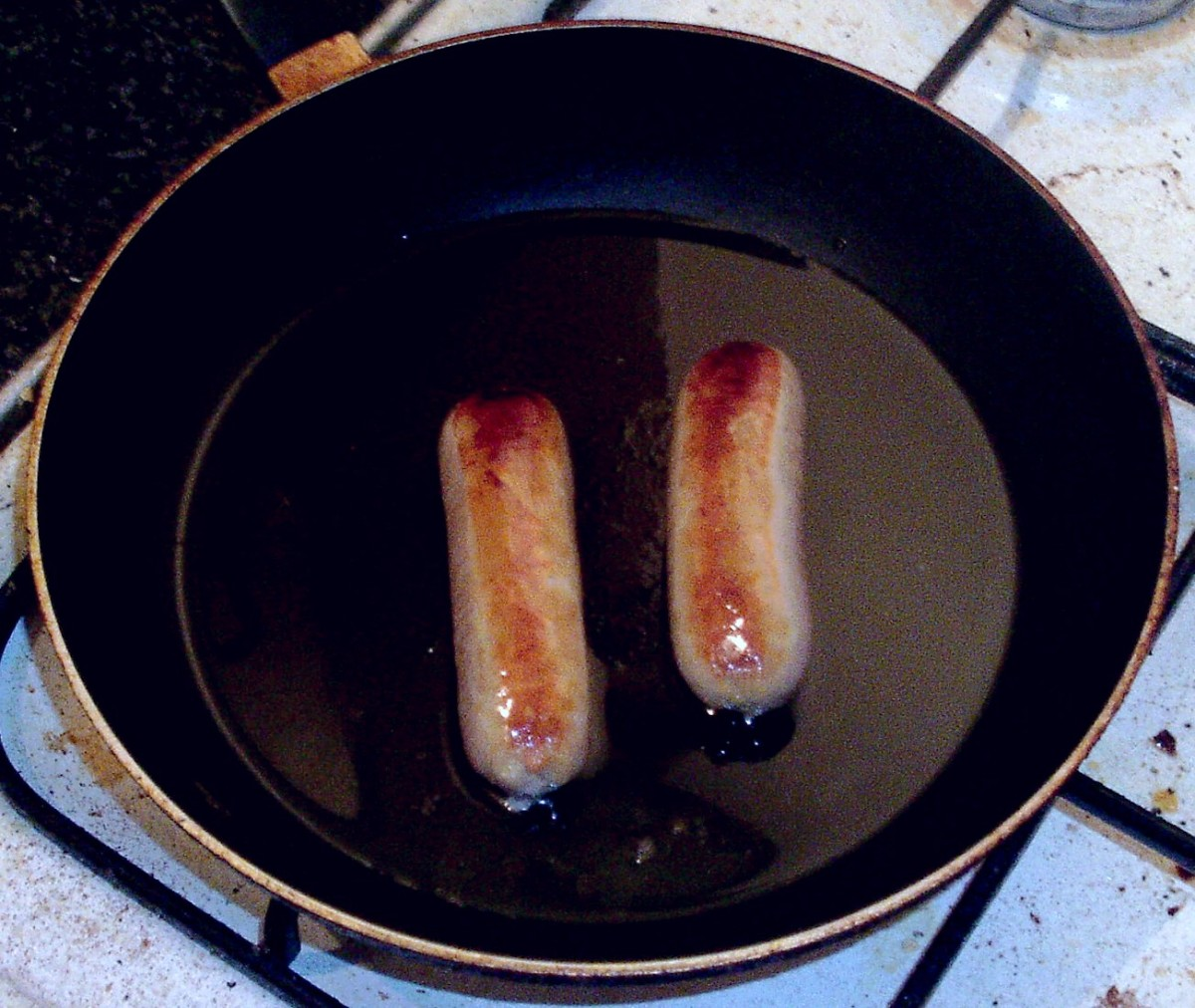 Chicken sausages are turned regularly in the pan as they fry