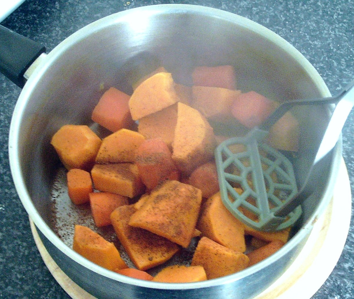 Mashing sweet potatoes and carrot