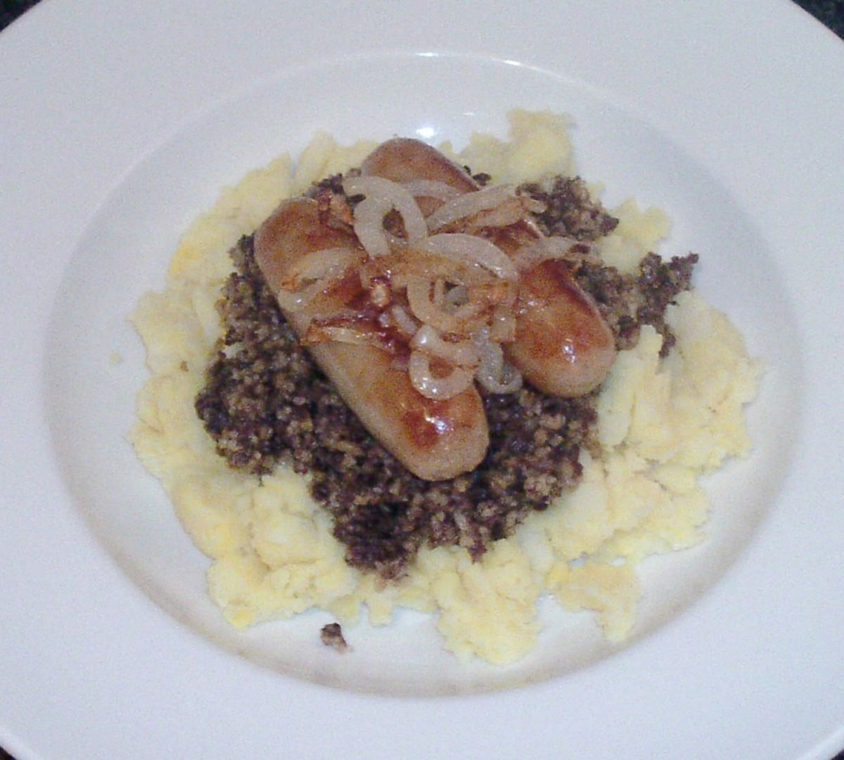 Chicken sausages are served on a bed of haggis and mustard mash, topped with fried onions