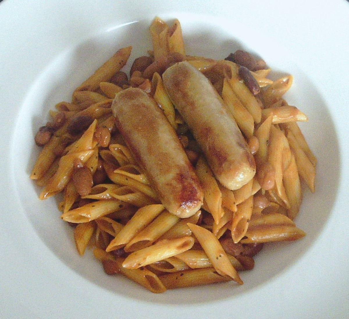 Chicken sausages are served on a bed of penne pasta in five bean and tomato sauce