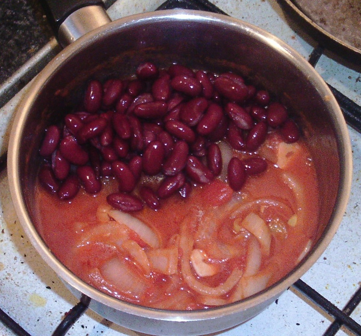 Kidney beans are added to tomatoes and onion