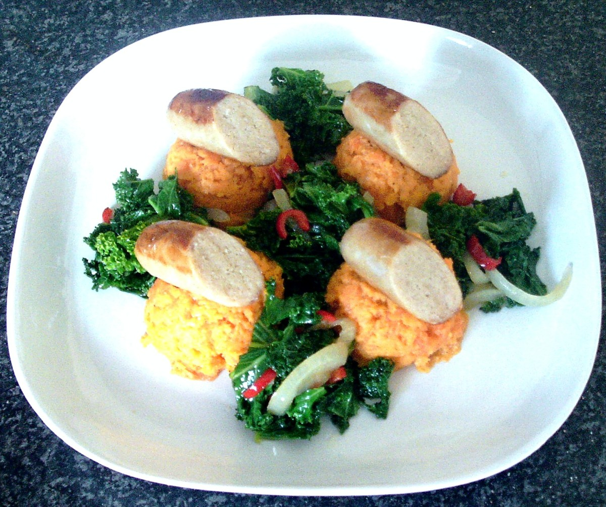 Chicken sausage halves are arranged on scoops of sweet potato and carrot mash, served with chilli and garlic spiced sauteed kale