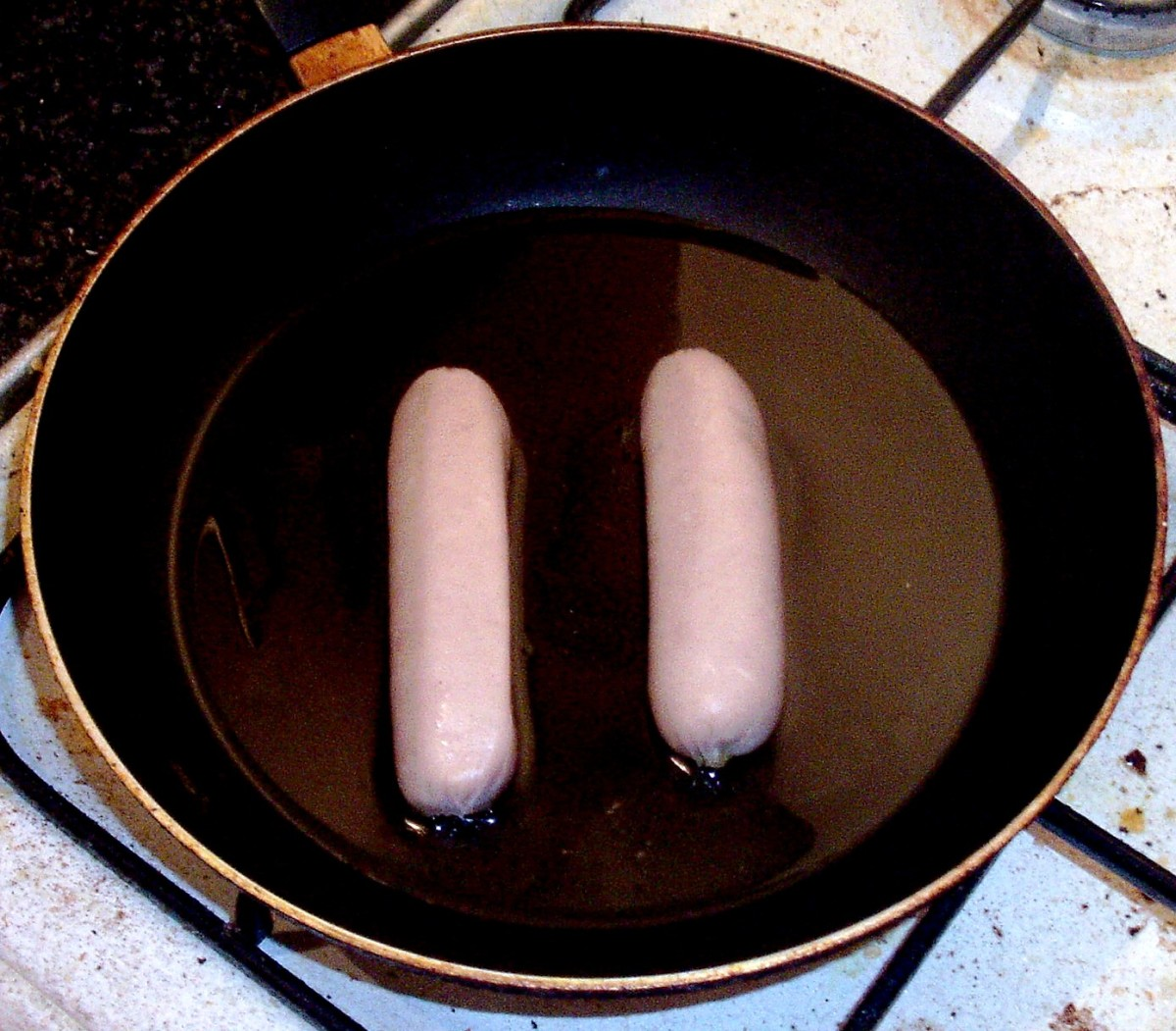 Chicken sausages are added to a frying pan with a little vegetable oil