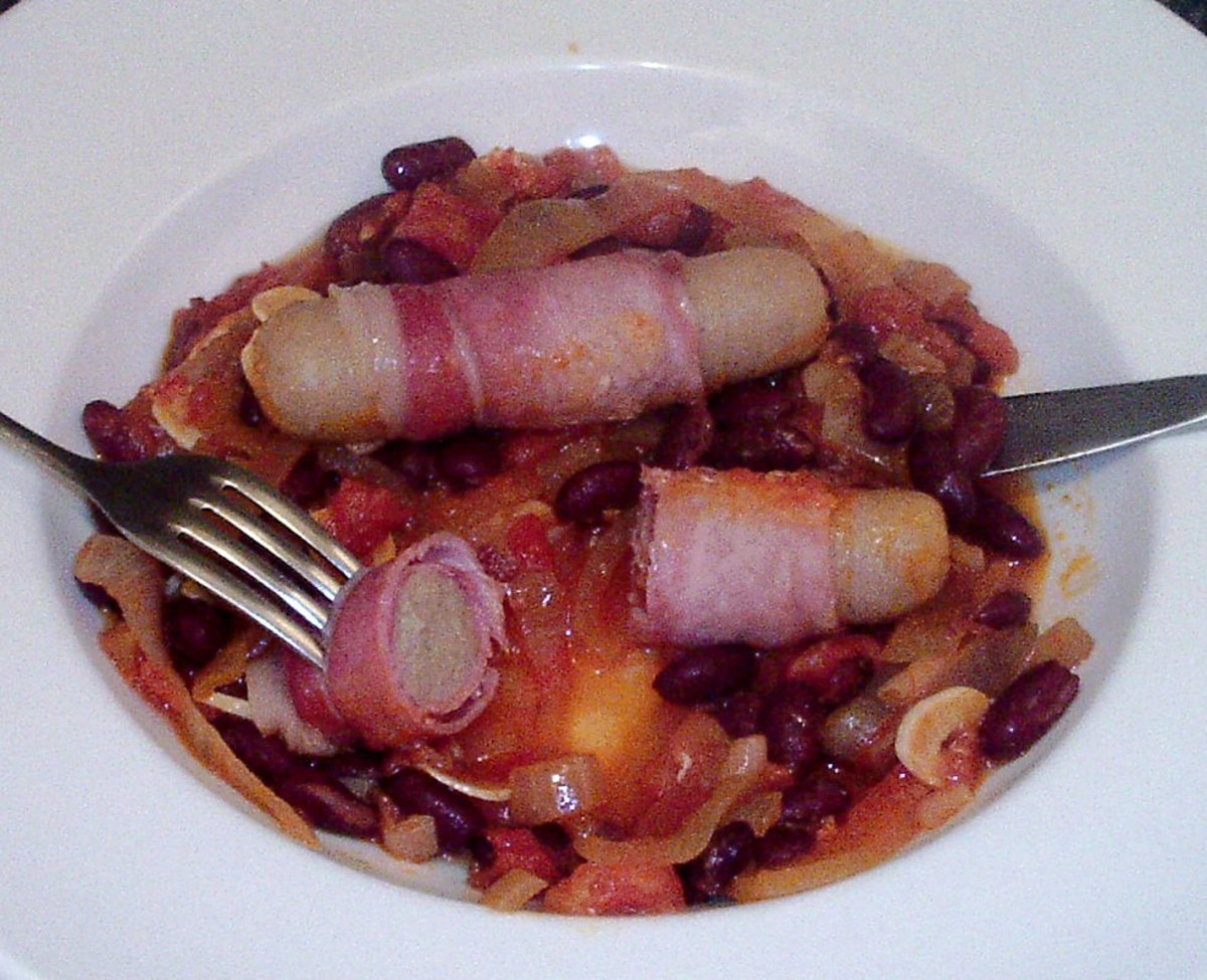 Casseroled chicken sausages in bacon served on a bed of spicy beans