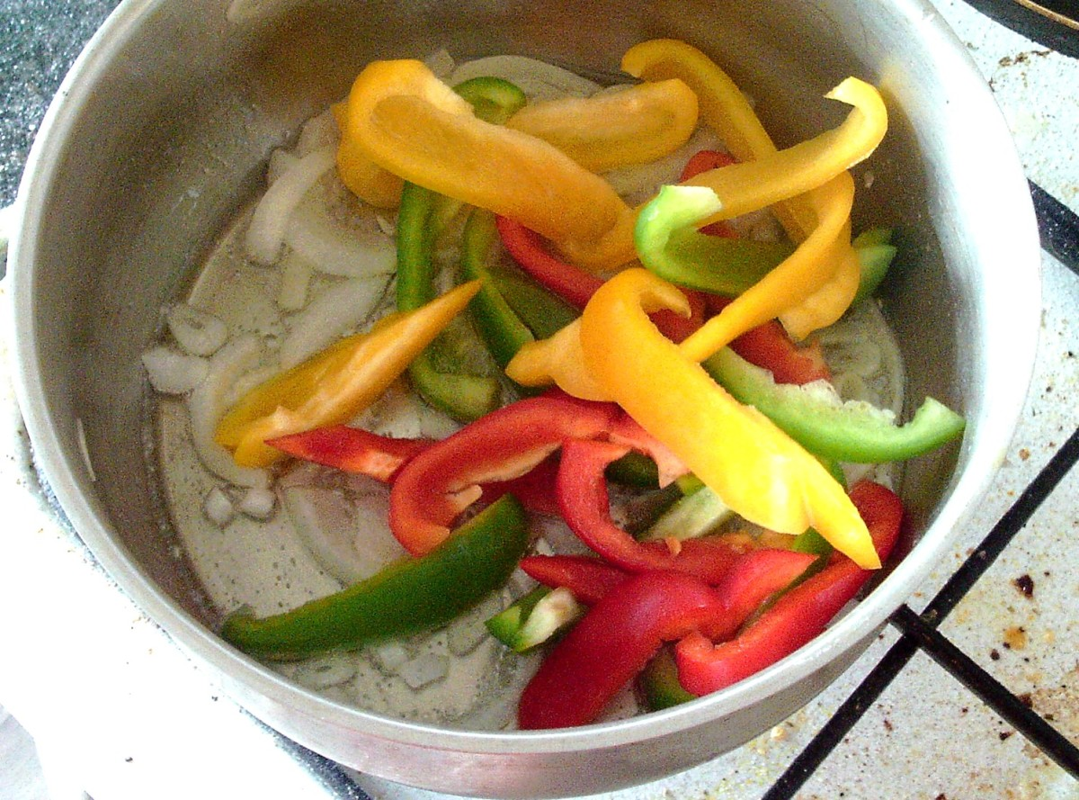 Sliced peppers are added to sauteed onion and garlic